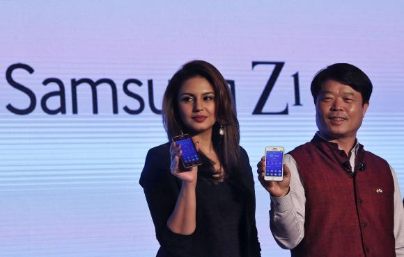 Hyun Chil Hong, president and chief executive of Samsung India Electronics, and Bollywood actress Qureshi hold the Samsung?s new Z1 smartphones at its launch in New Delhi